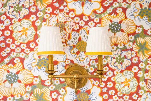 beekman light fixtures against floral red wallpaper.