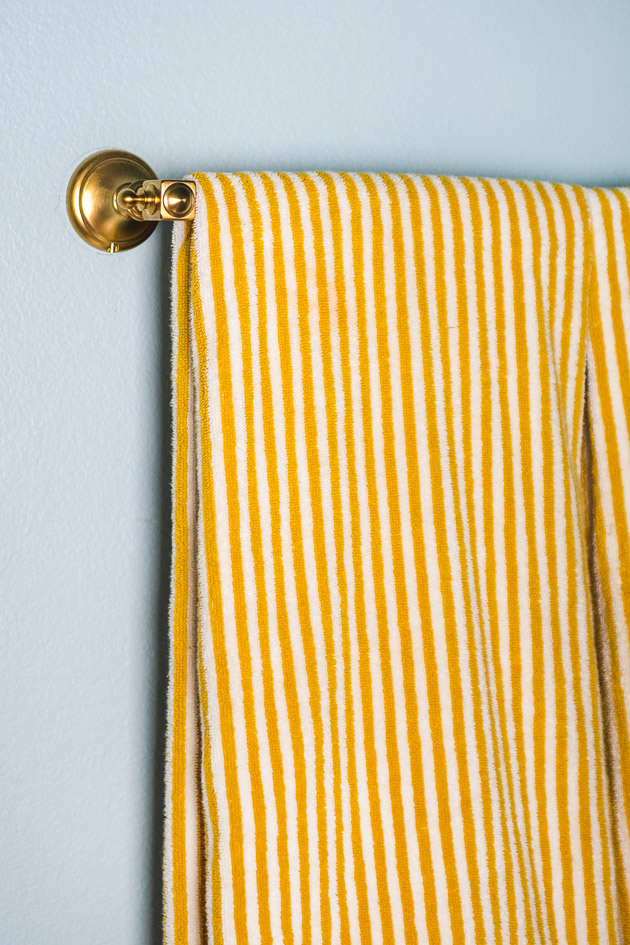 A yellow striped towel hanging on a brass towel rack.