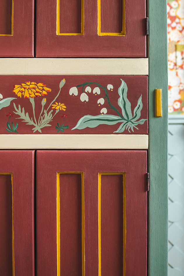 A painted cupboard. It is burgundy with green, mustard, and white accents.