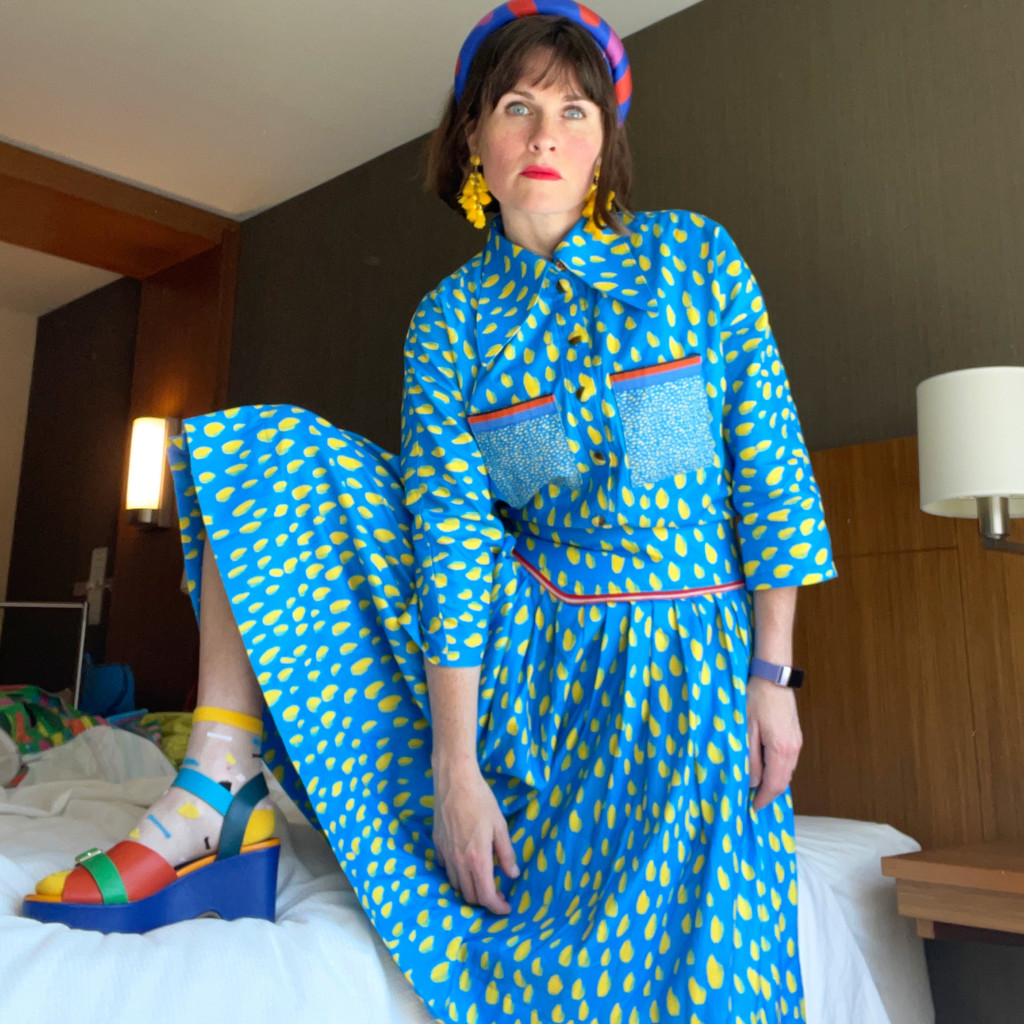 Katie wears a blue dress with painterly yellow marks and red details. Her earrings are yellow, her headband is blue with red splotches, and she's wearing blue and green wedge sandals with red and yellow socks underneath.