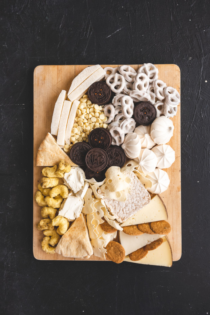 A ghost shaped Halloween snack board. It includes oreos, yogurt-covered pretzels, merengues, jicama, white chocolate chips, pita slices, ghost-shaped potato crisps, rice puffs, cheese, goat cheese, and crackers.