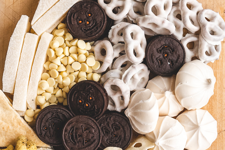 Closeup of a ghost shaped Halloween snack board. It includes oreos, yogurt-covered pretzels, merengues, jicama, and white chocolate chips.