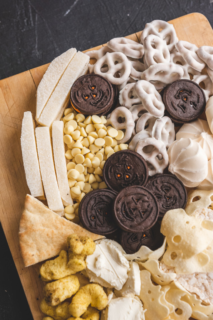 Closeup of a ghost shaped Halloween snack board. It includes oreos, yogurt-covered pretzels, merengues, jicama, white chocolate chips, pita slices, ghost-shaped potato crisps, rice puffs, cheese, goat cheese, and crackers.