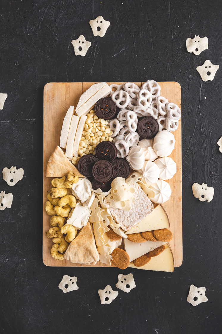 A ghost-shaped halloween snack board on a black background.