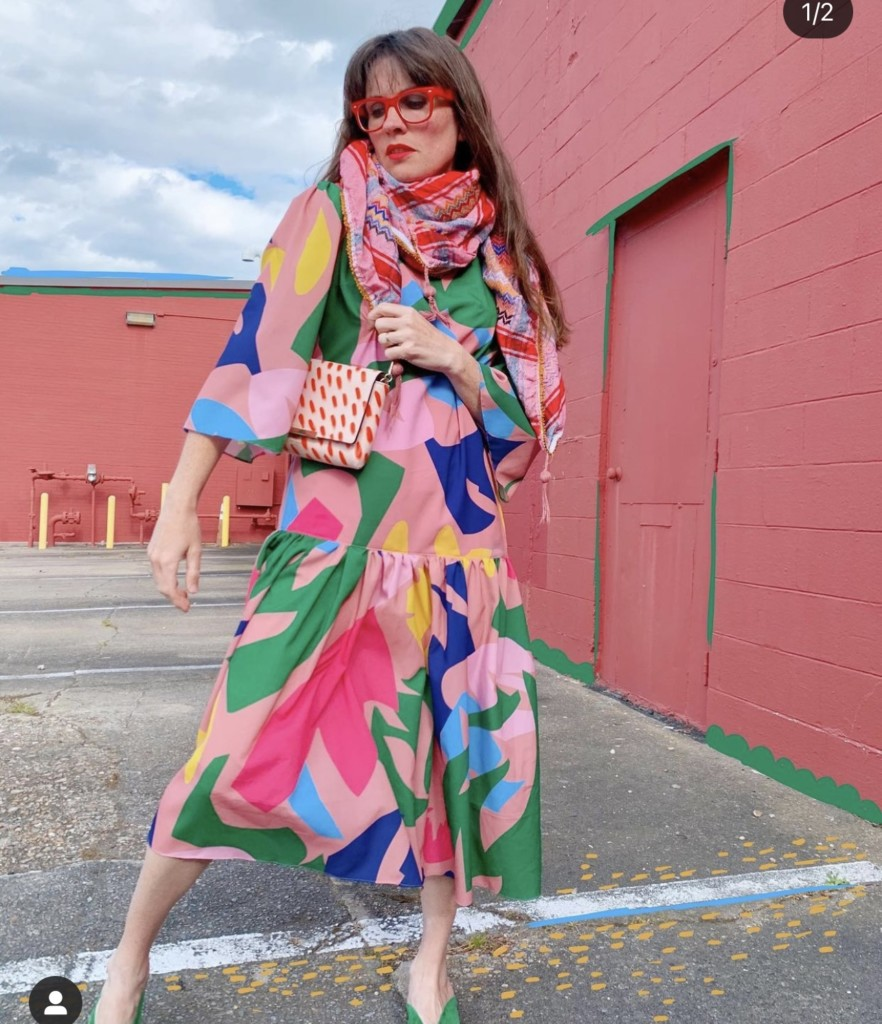A woman models a dress next to a red building. The dress is pink with large abstract shapes in magenta, blue, cobalt, and bright green.