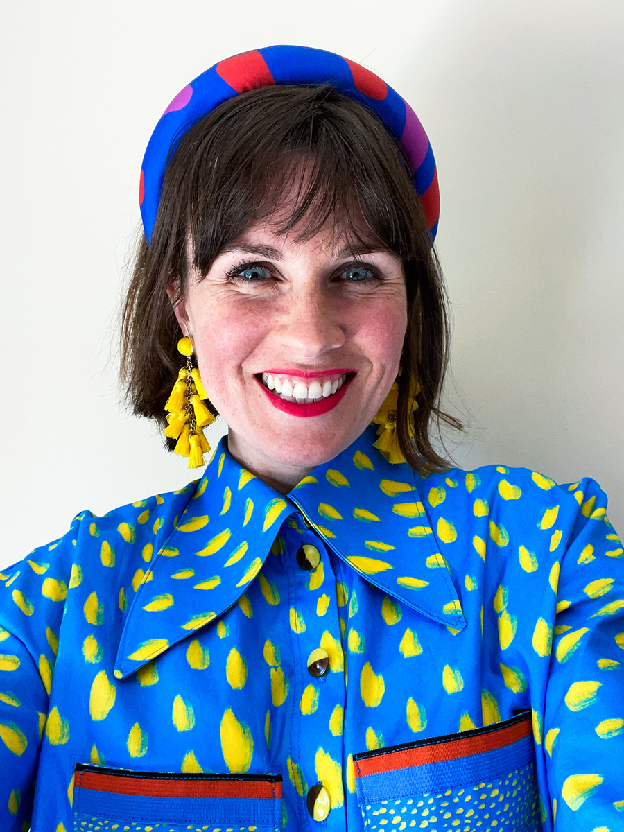 Katie Kortman wearing a blue blouse with yellow and red accents and a blue headband with red accents, smiles at the camera.