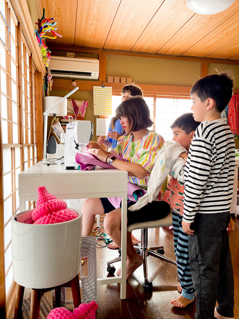Katie Kortman and her kids sit around a sewing machine and work on a project.