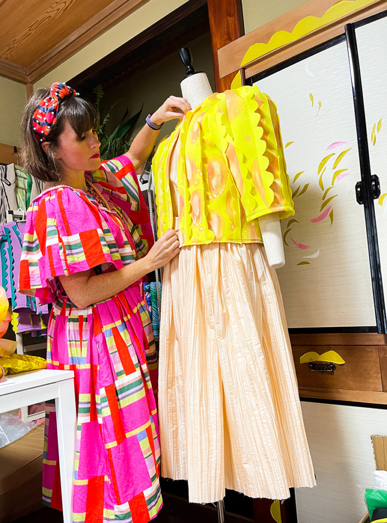 Katie works on a yellow jacket while standing by a dress model. Katie's wearing a pink, red, yellow, and green colorful dress.