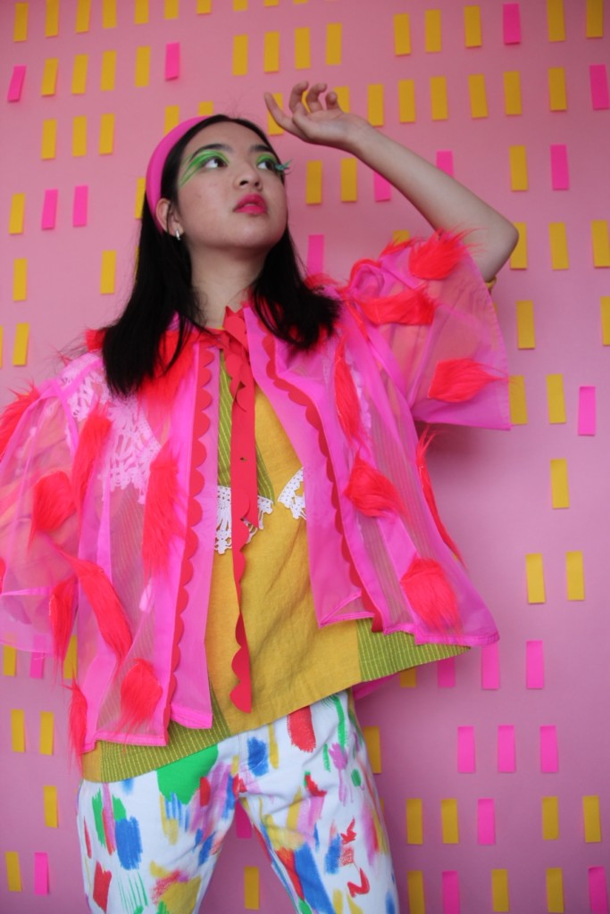 A model wears Katie's pink overjacket with a yellow top underneath and white pants with colorful details. The backdrop is pink with yellow and pink rectangles.