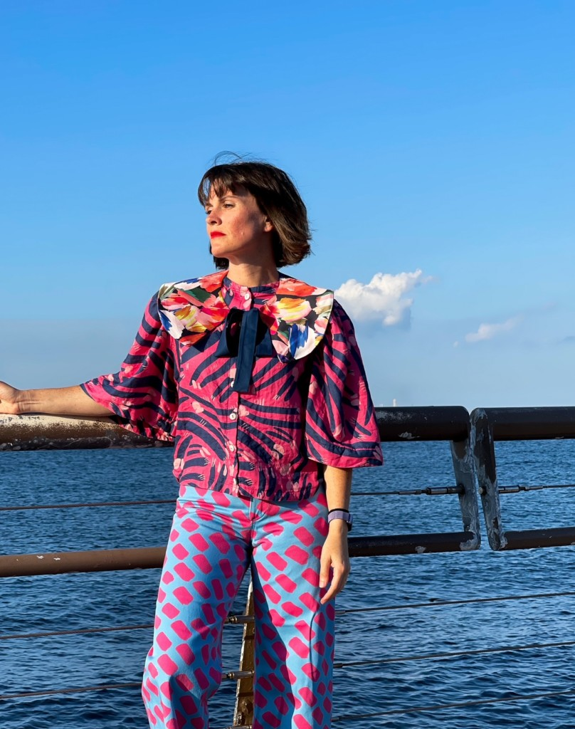 Katie Kortman wearing bright prink and blue pands and a blouse standing by the ocean.