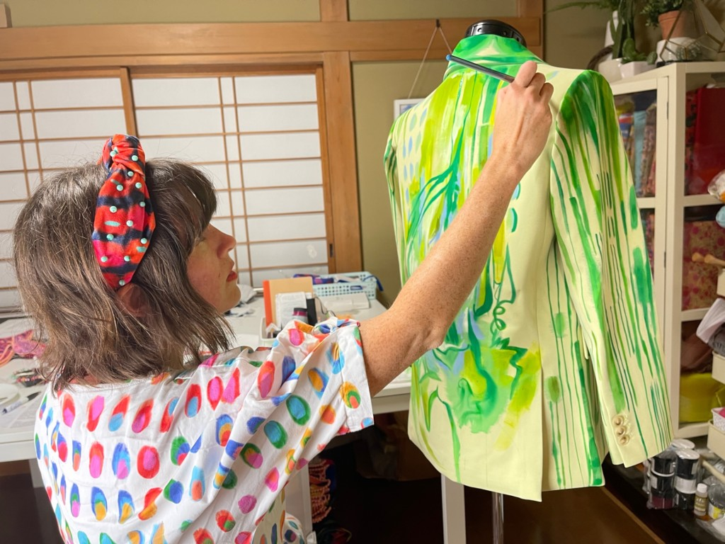 Katie stands by a dress model working on a green blazer design.