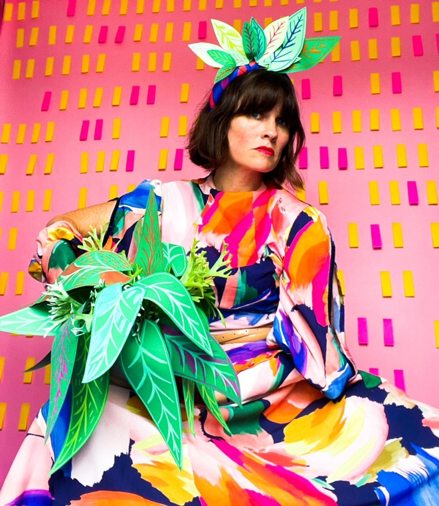 Katie Kortman modeling a vibrant dress and holding fabric plants in front of a pink wall