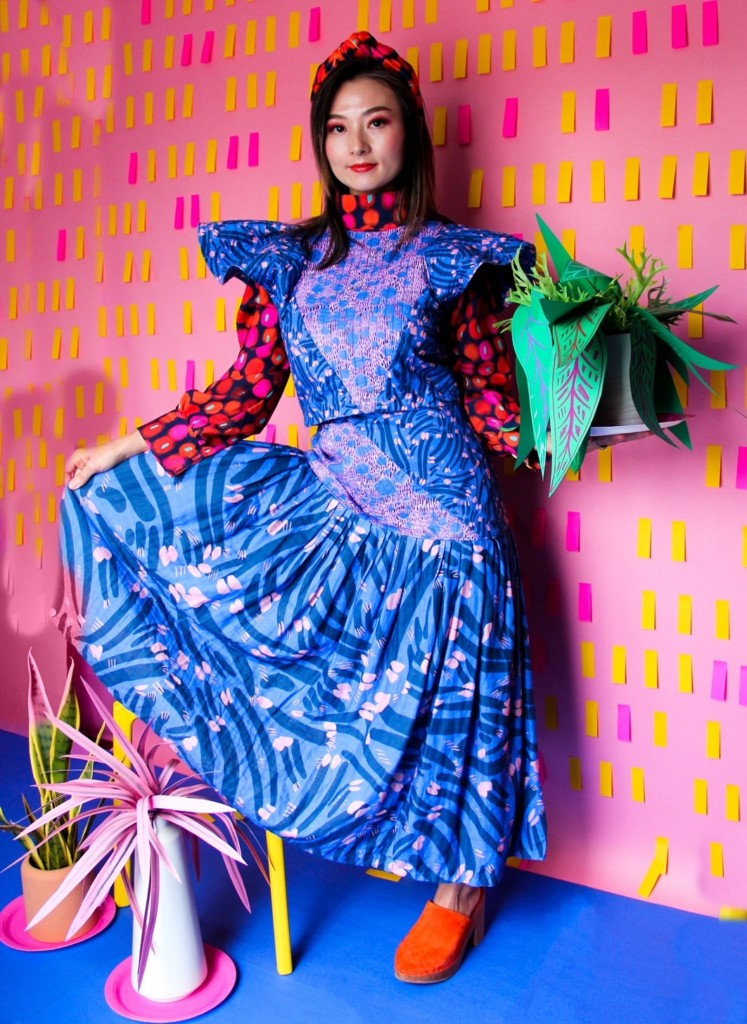A woman models one of Katie Kortman's designs – a blue and purple dress– while holding a plant.