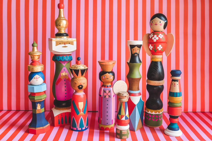 Midcentury painted heirloom nativity figures against a pink and red striped background.