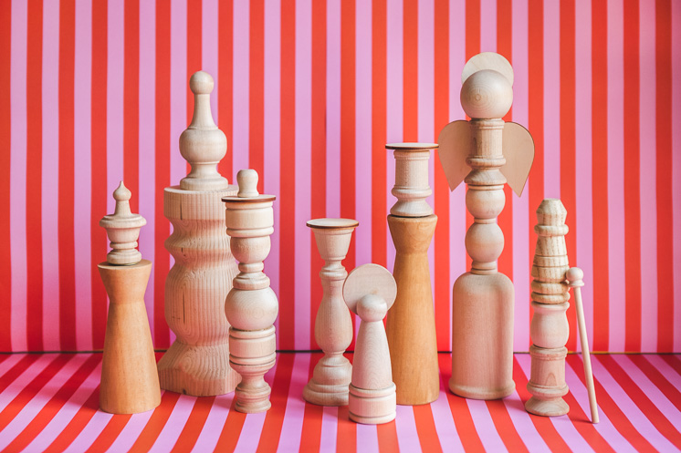 unpainted wooden finials and candlesticks in the form of wooden nativity characters