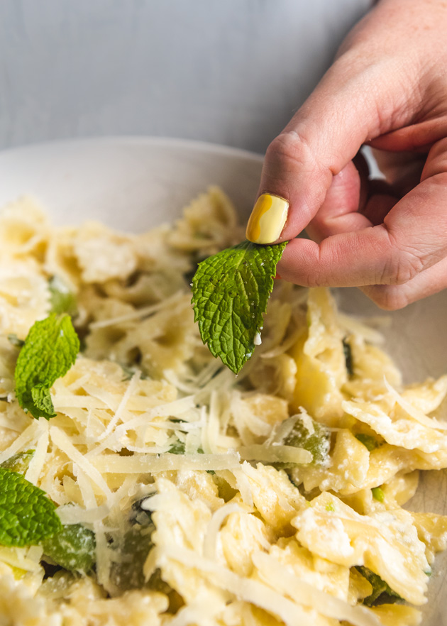 Brittany puts a mint leaf into a bowl of bowtie pasta with peas and cheese. She has a yellow-painted thumbnail.