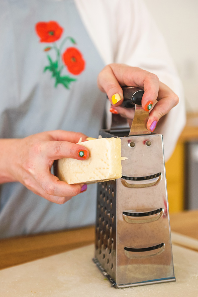 Brittany grates cheese while wearing a light blue apron with red poppies.