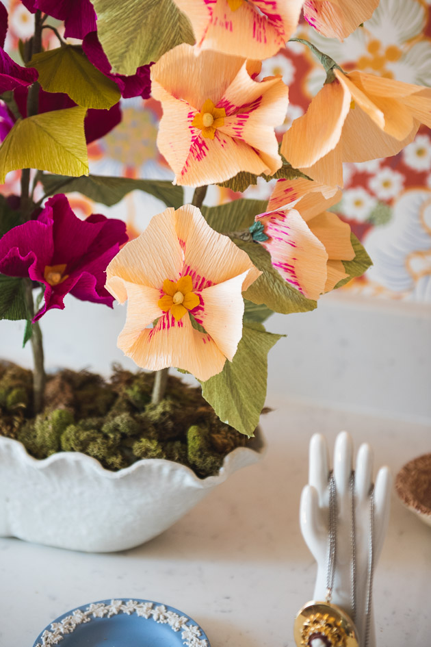 paper hollyhocks on a bathroom counter among ceramic odds and ends with a mirror and red floral wallpaper in the background.