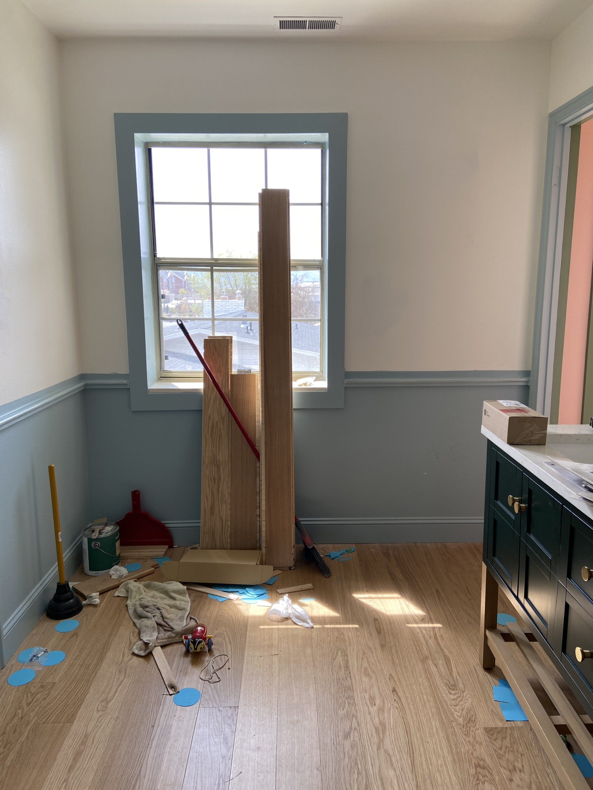 Interior shot of a bathroom with wooden floors and blue and white walls. There's blue-painted trim at waist-height around the room, and some boards and materials are cluttered in the corner and under a window.