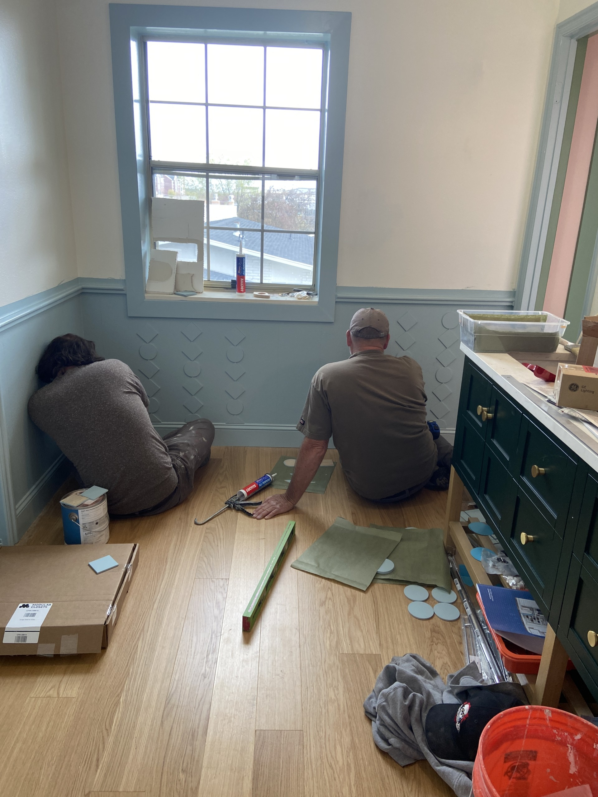 Two workmen glue up wooden cutouts as a custom DIY wainscoting.