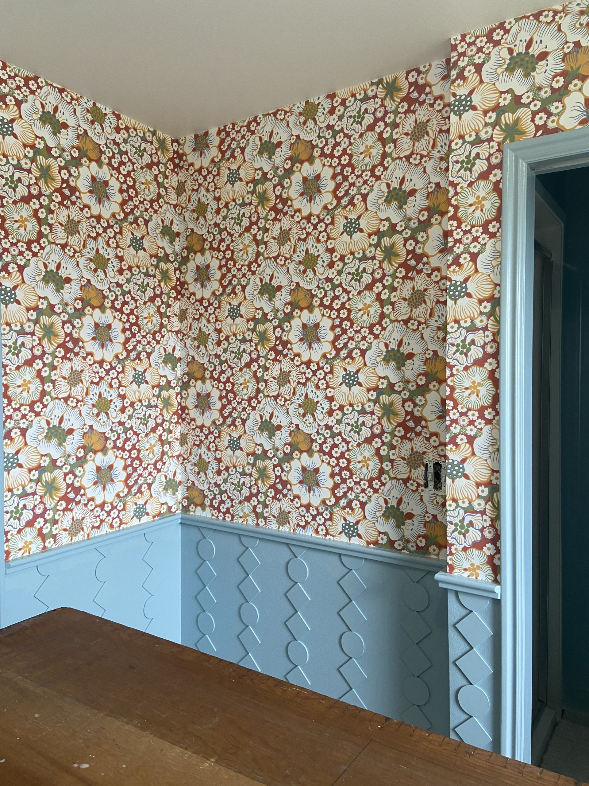 Interior shot of a room with red floral wallpaper and blue custom wainscoting.