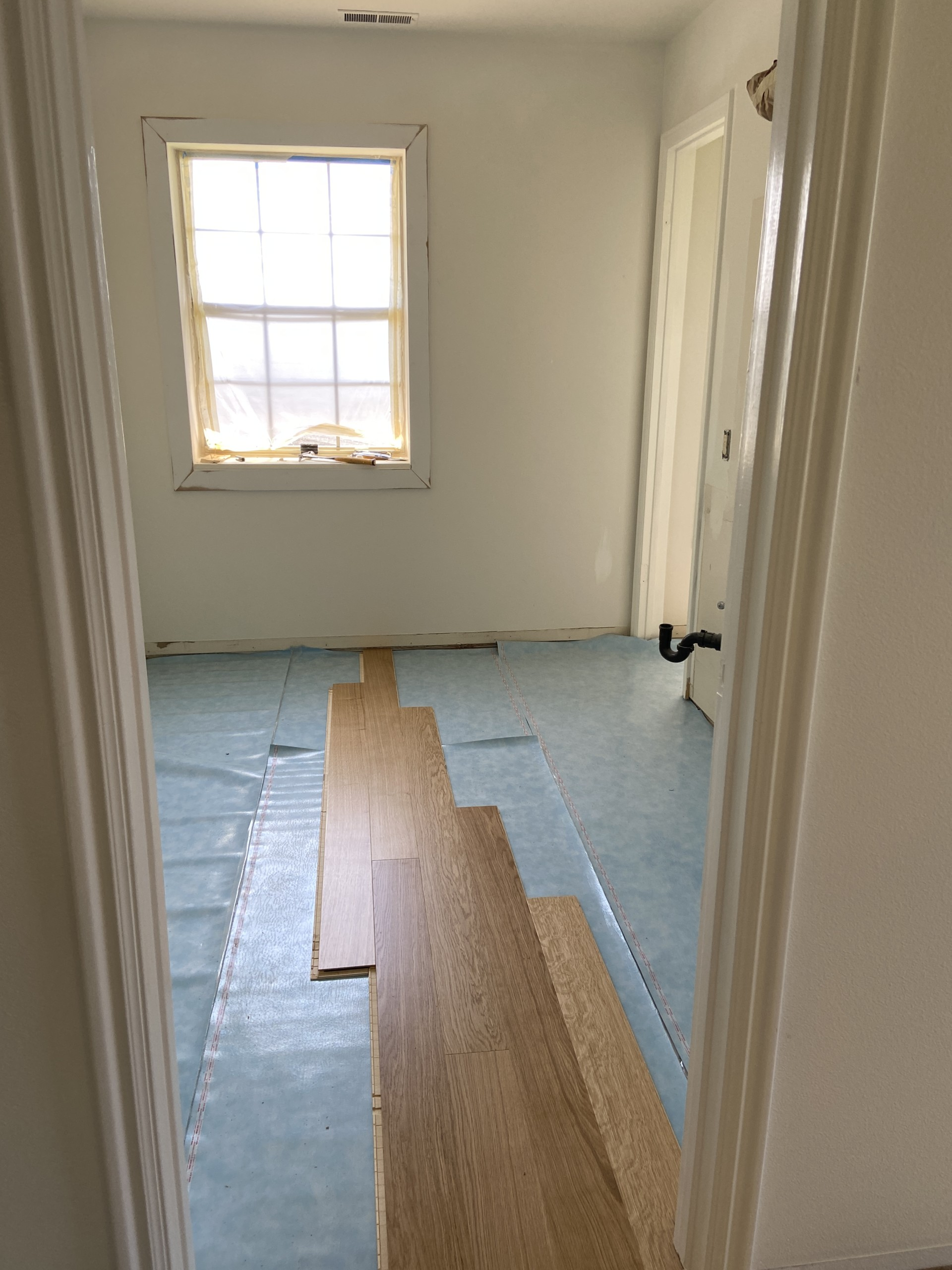 Vertical image of the bathroom. There's warm wooden flooring being laid over light blue plastic sheeting.