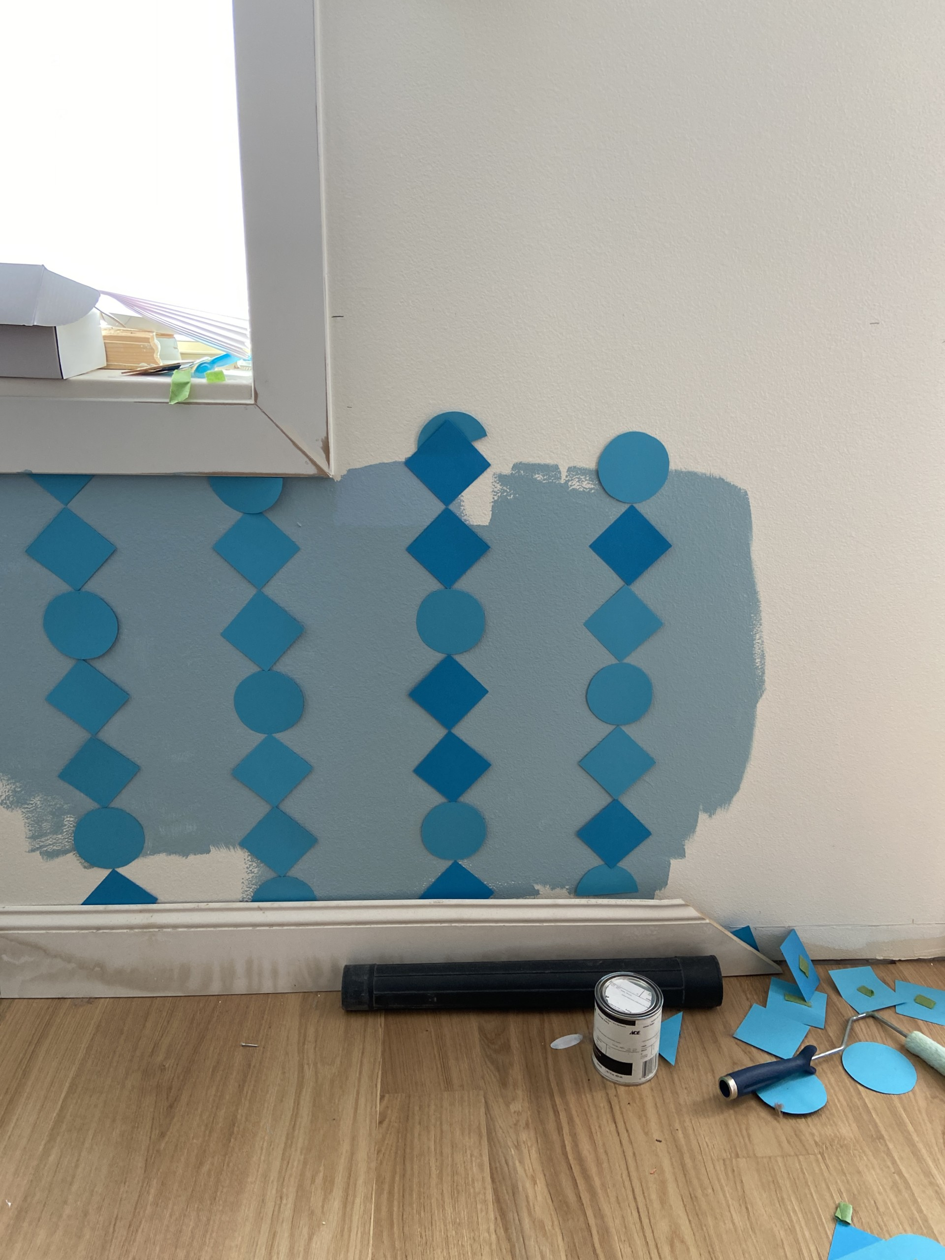 Paper mockup of DIY wainscoting on a white and blue wall.