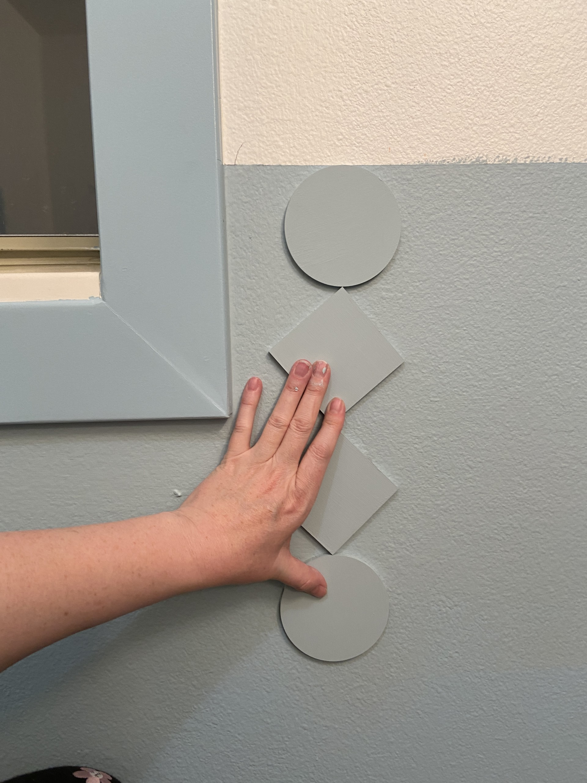 A hand reaches into frame from the left and holds up blue painted cutouts against a blue and white wall.