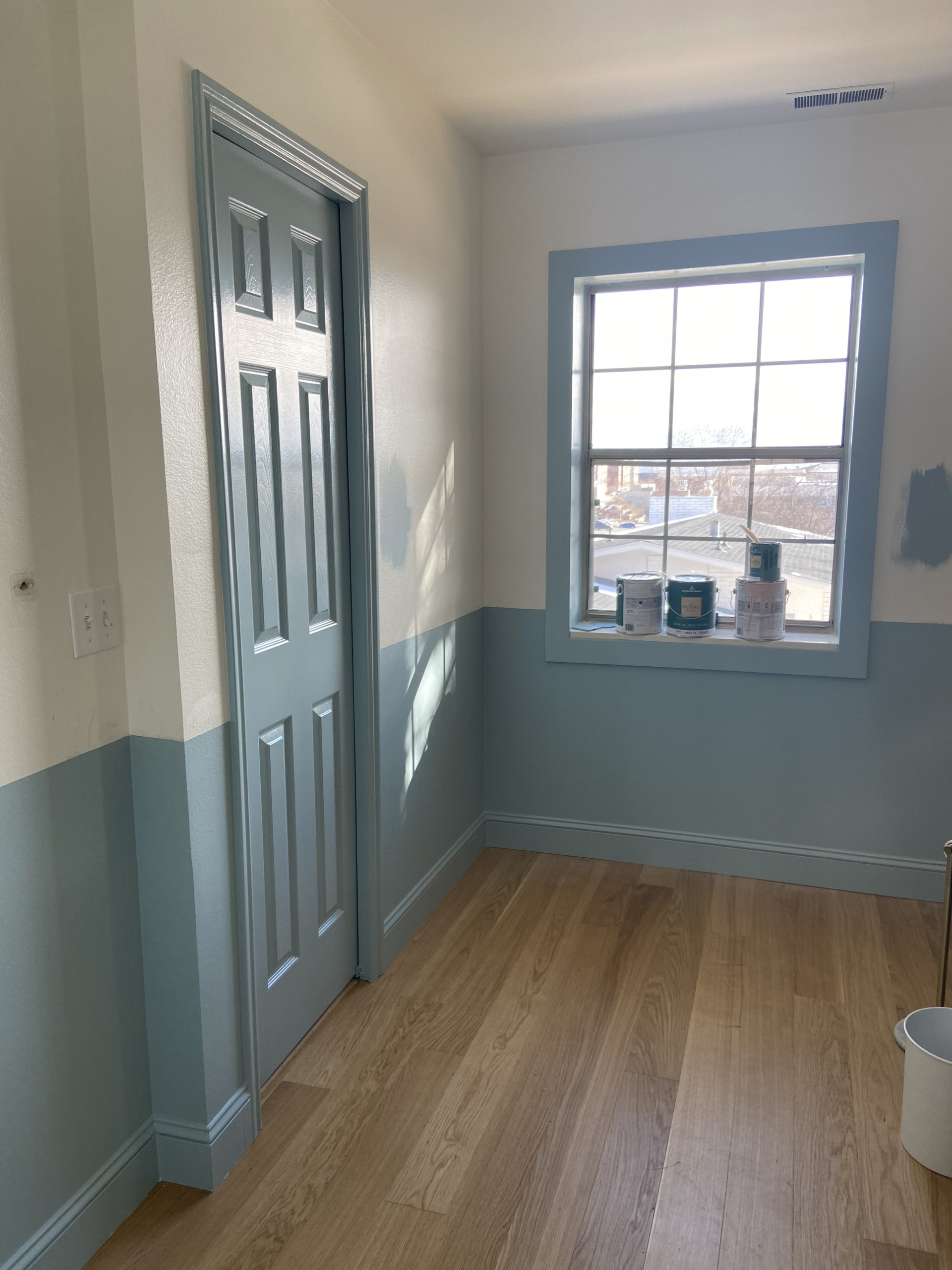 Interior shot of a room with wooden floors and blue and white walls.