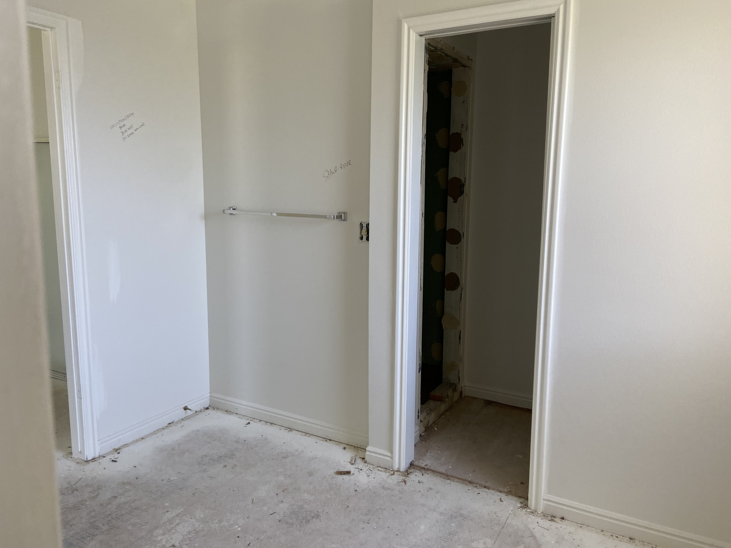 a blank, unfinished room with sheetrock walls and a dusty subfloor. There's a doorway that leads to a dark, grey space in the image