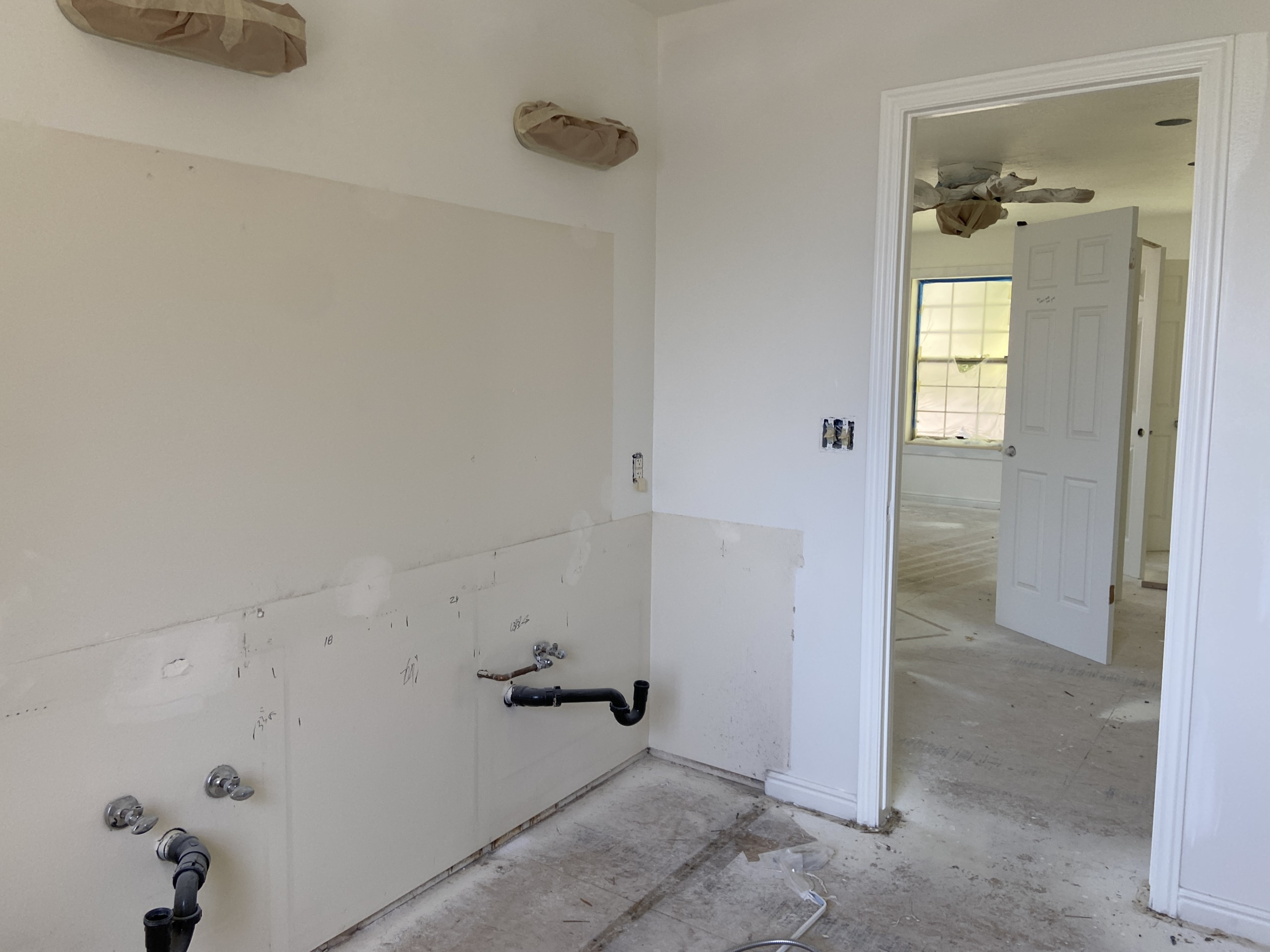 a blank, unfinished room with sheetrock walls and a dusty subfloor. There's a doorway that leads to another unfinished space in the image. One of the walls has mysterious plumbing coming out of it.