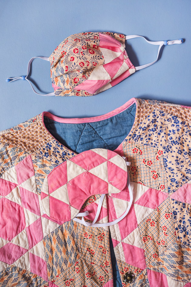a face mask, eye mask, and matching quilted coat on a blue background.