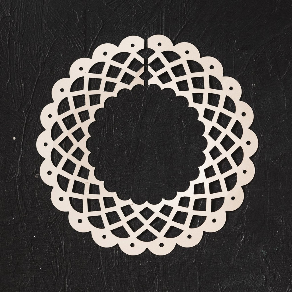 A white paper lace collar on a black background.