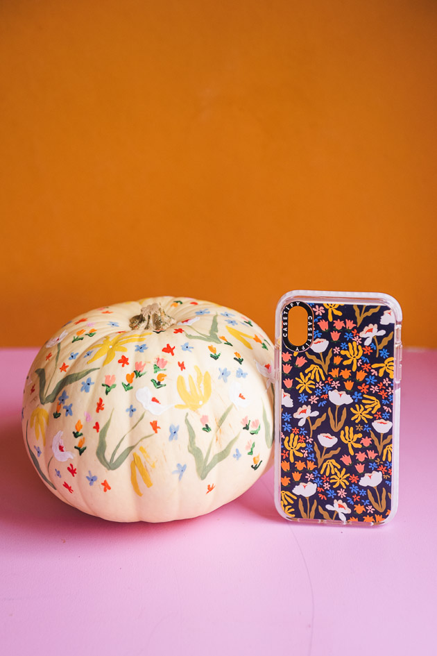 delicate floral painted pumpkin on a pink and orange background. There's a matching phone case next to it.