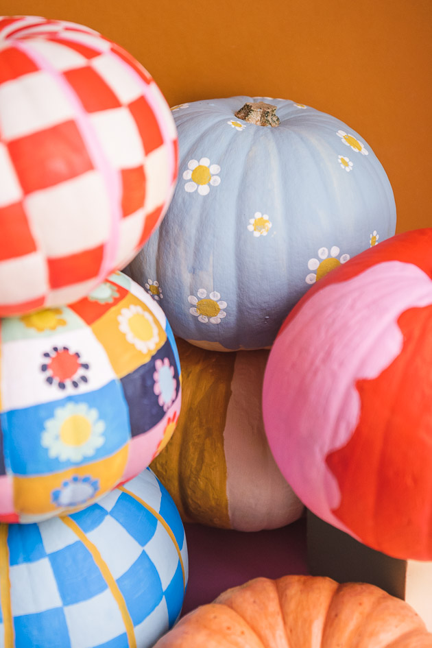 A clump of painted mini pumpkins in bright colors.