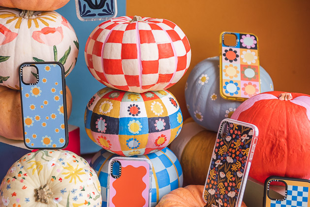 Stacks of painted pumpkins on an orange and pink background.